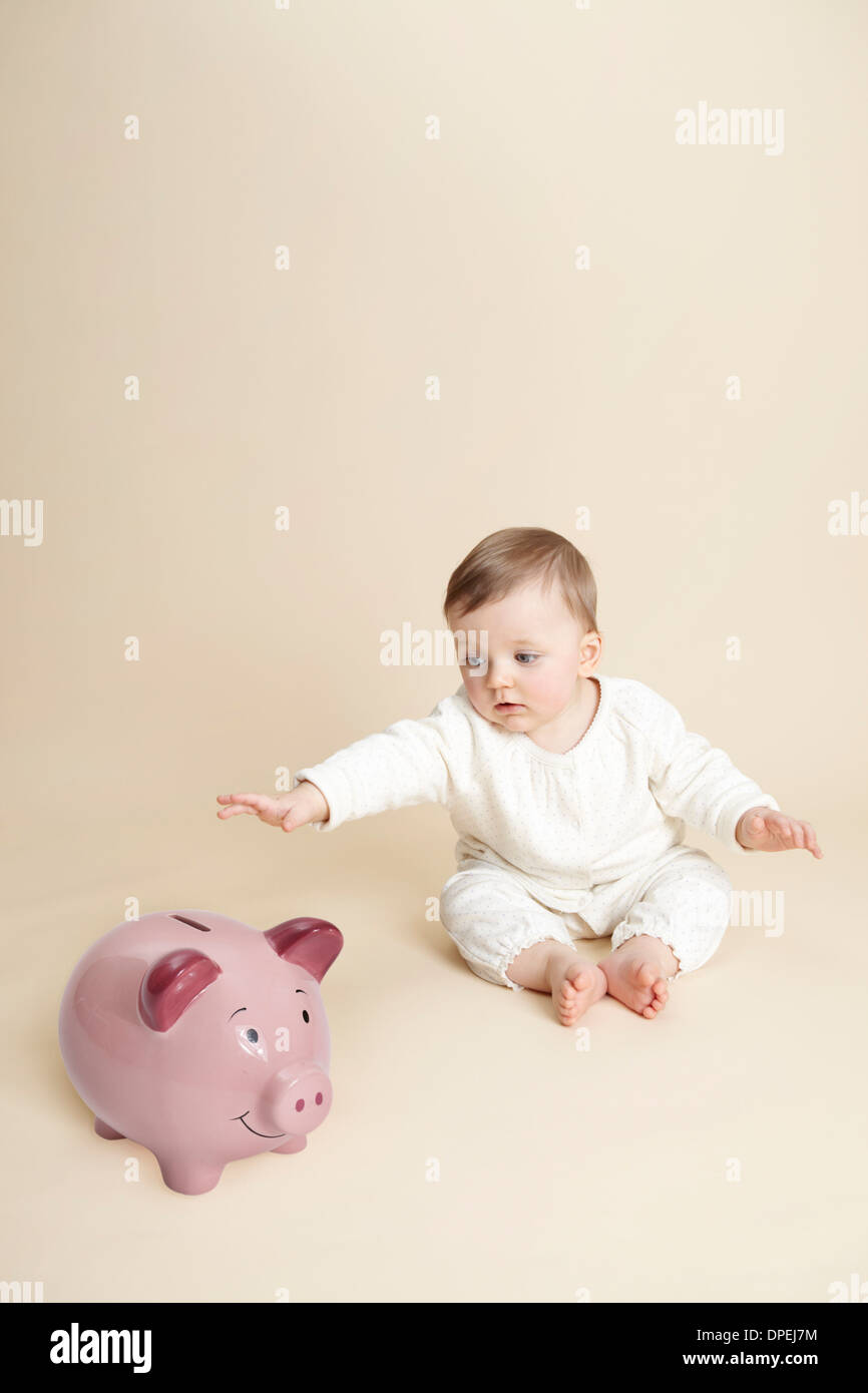Studio portrait of baby girl reaching for piggy bank - Stock Image