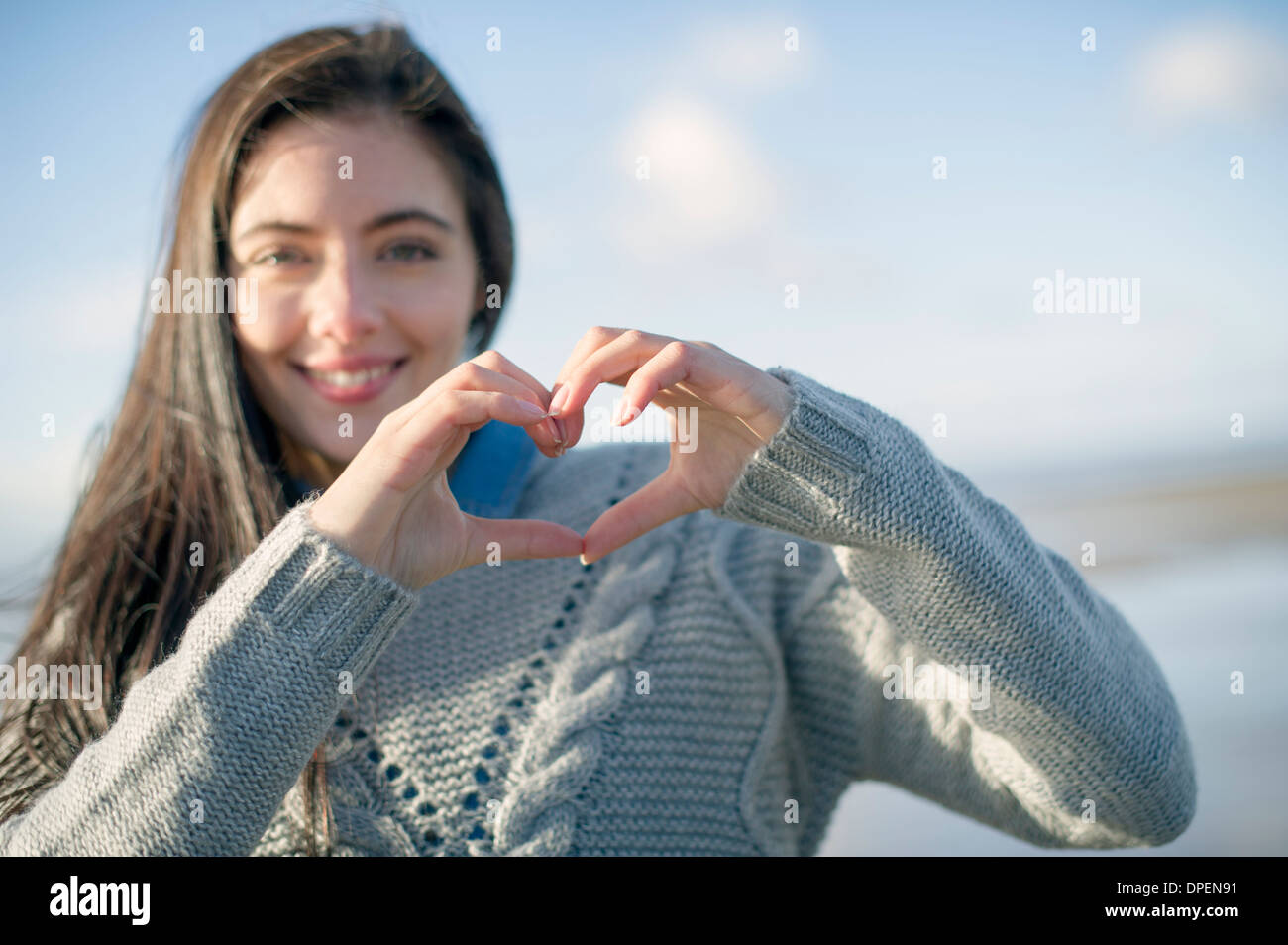 Young woman making heart shape with hands - Stock Image