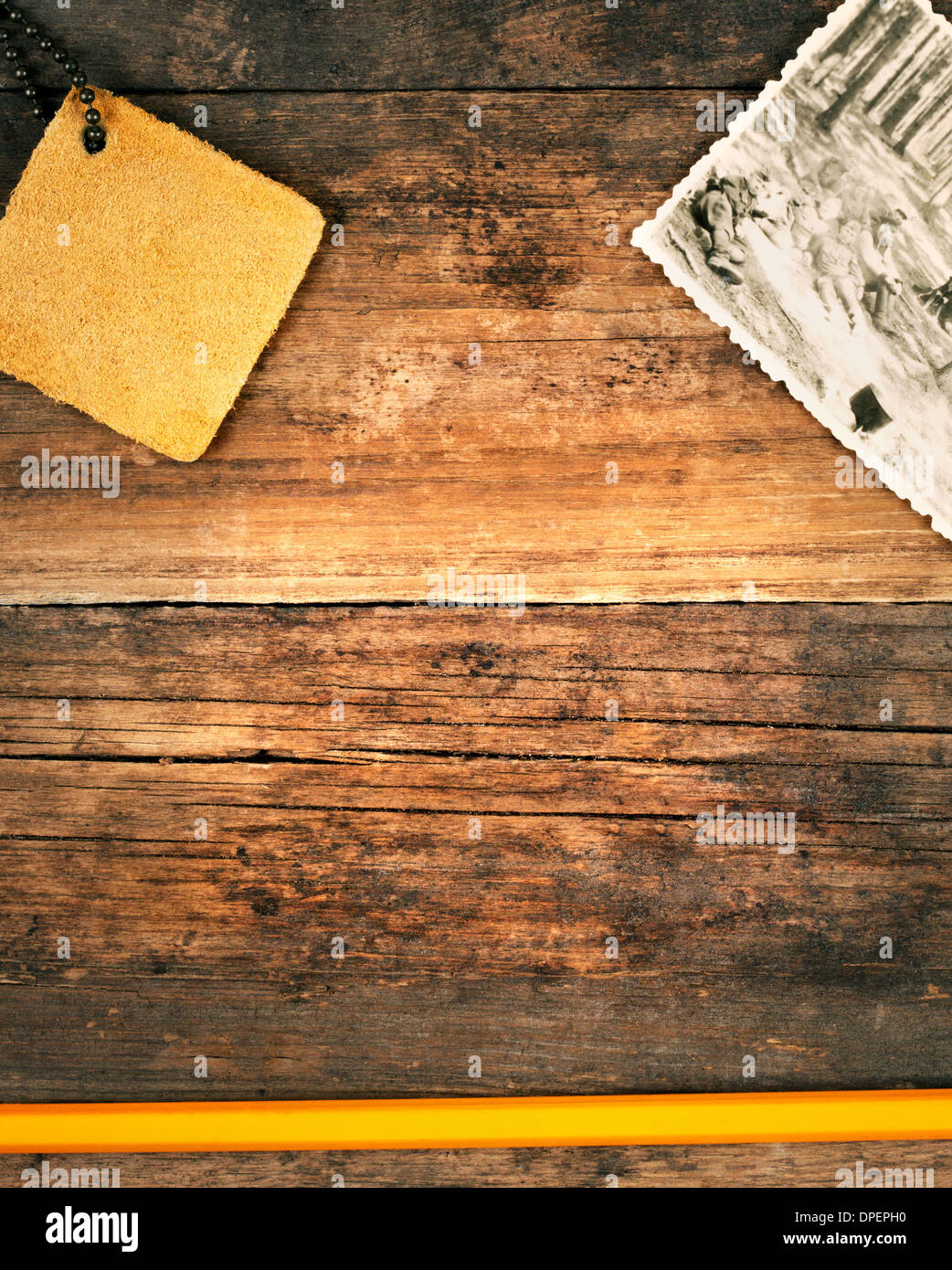 Background of old weathered planks with a photo and a pencil - Stock Image