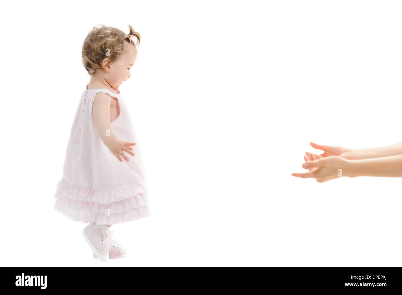 first steps of baby girl towards her mother's arms Isolated - Stock Image