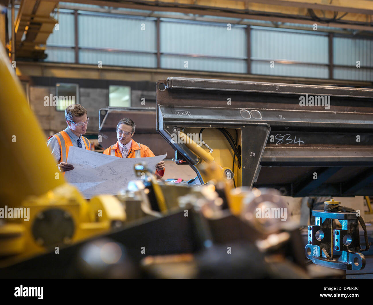 Engineers inspecting engineering drawings together in factory - Stock Image