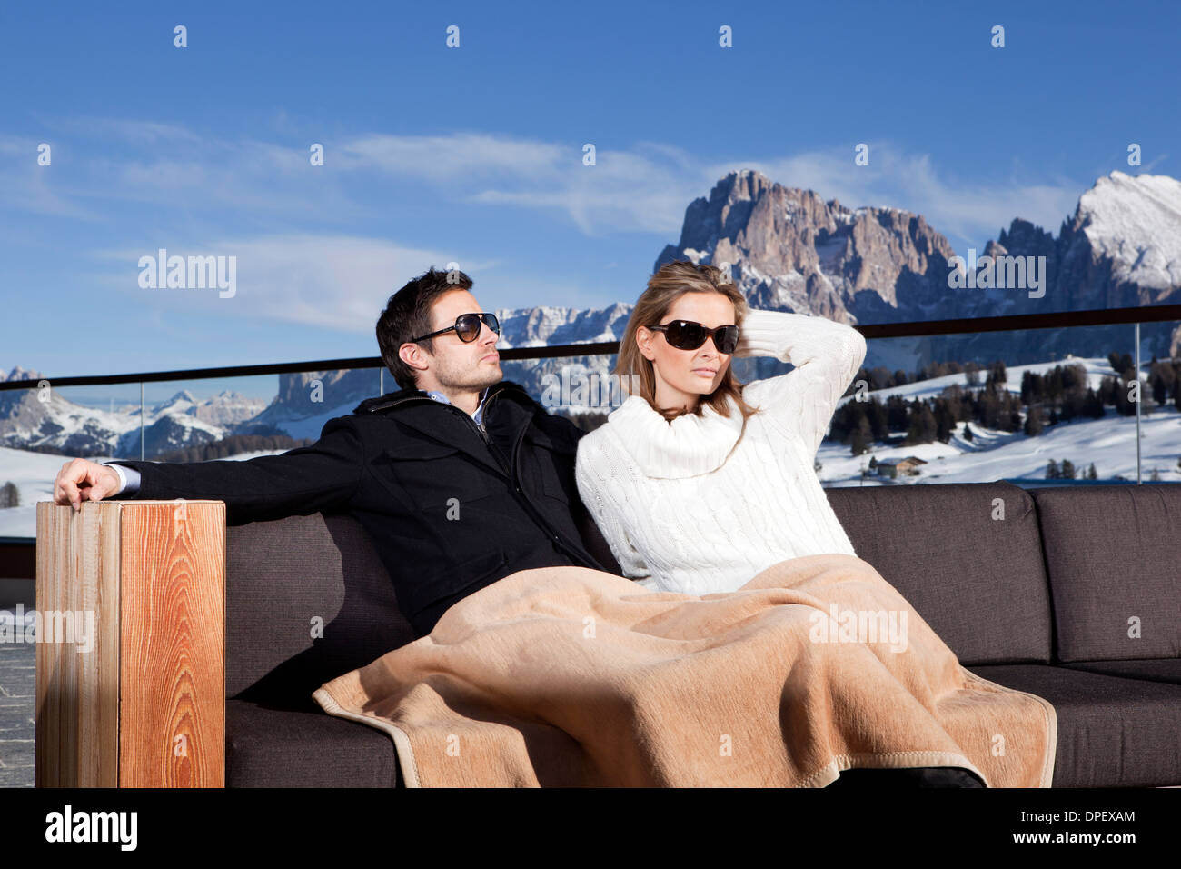 Man and woman sitting on a couch outdoors, Seiser Alm, South Tyrol, Italy - Stock Image