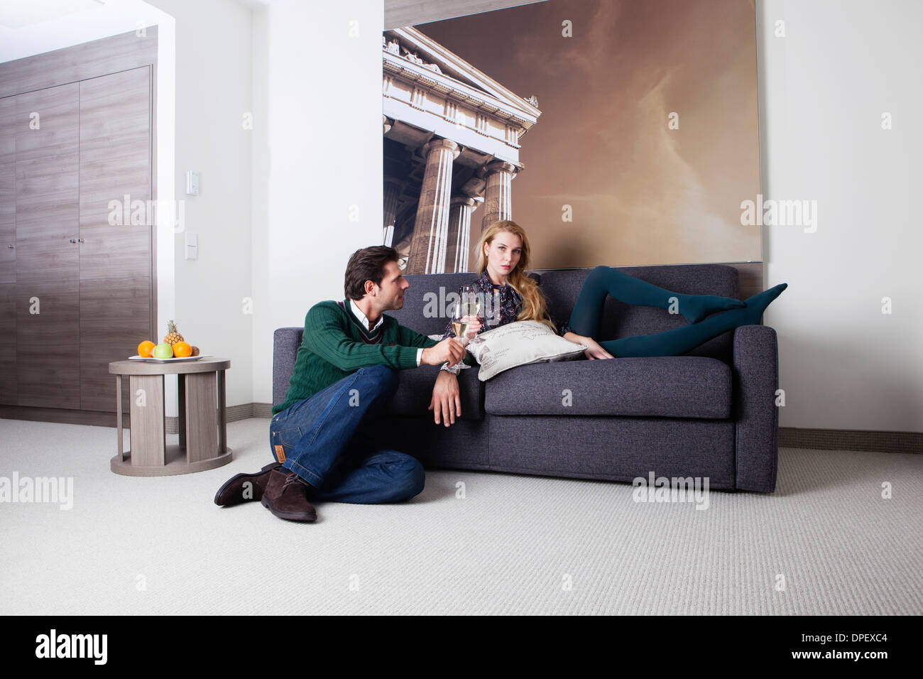 Man and woman on a couch in a hotel room - Stock Image