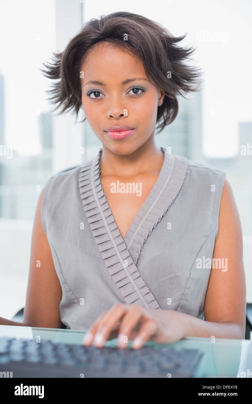 Unsmiling businesswoman working on computer while looking at camera - Stock Image