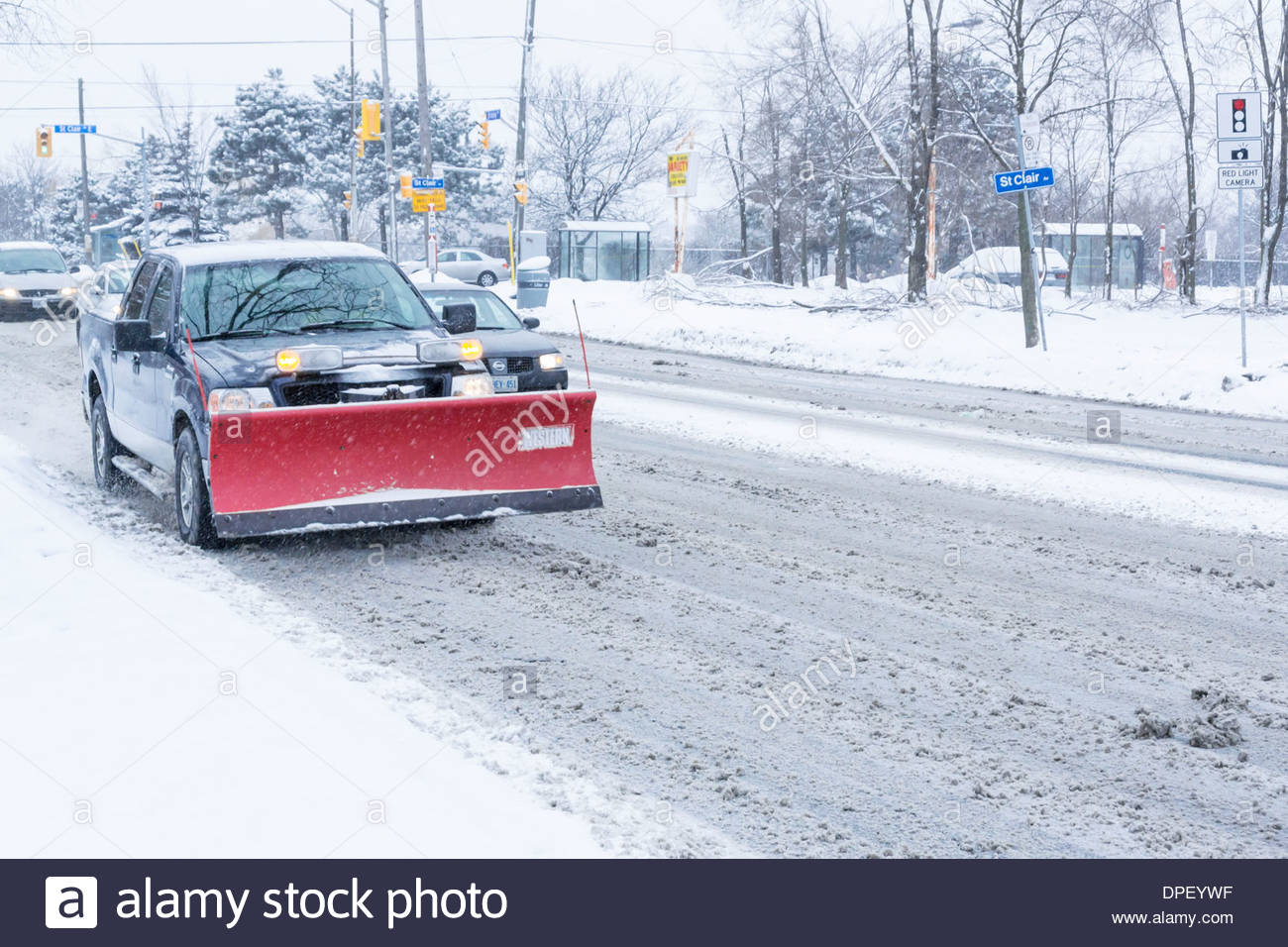 Snowplow on day so cold that salt ineffective in melting snow creating a slippery slush on road in Toronto Ontario Canada - Stock Image
