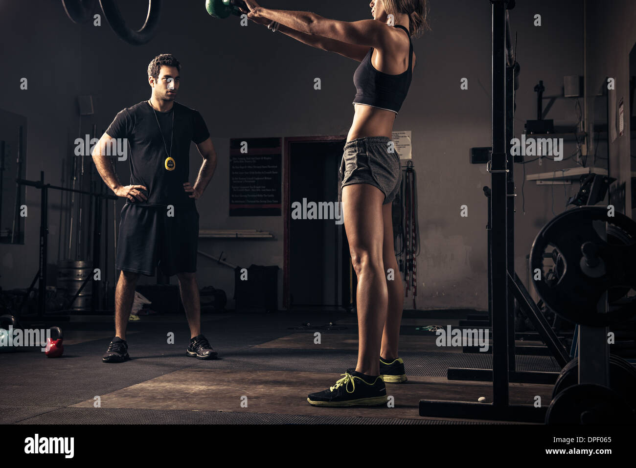 Female weight-lifter being watched by trainer - Stock Image