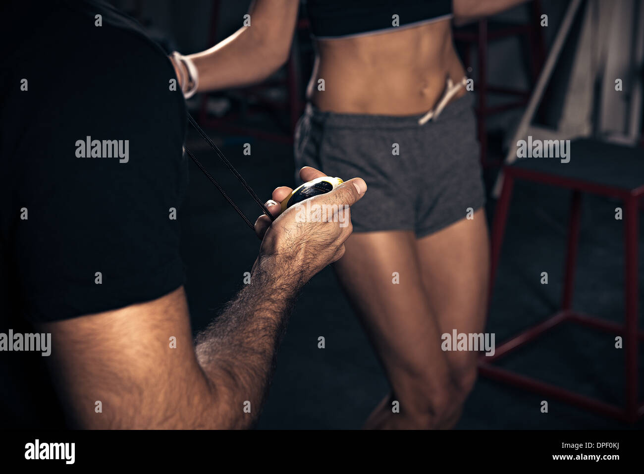 Woman being timed by trainer - Stock Image