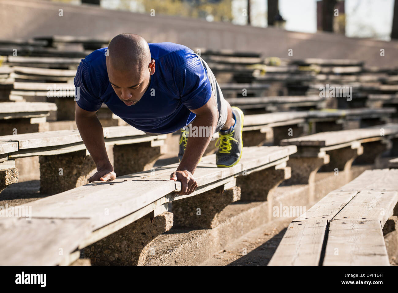 Man doing push ups on bench - Stock Image