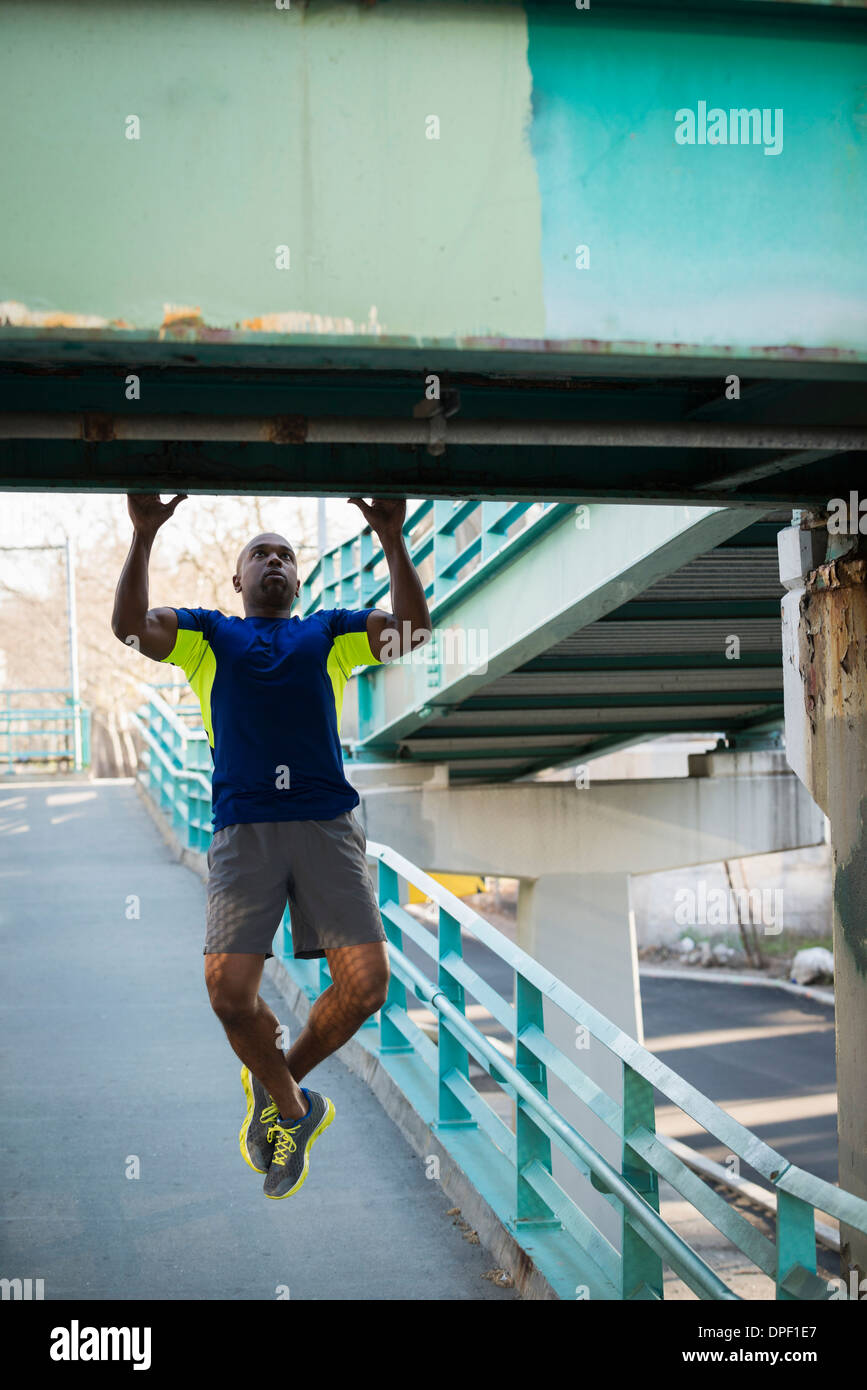 Man doing pull ups on bridge - Stock Image