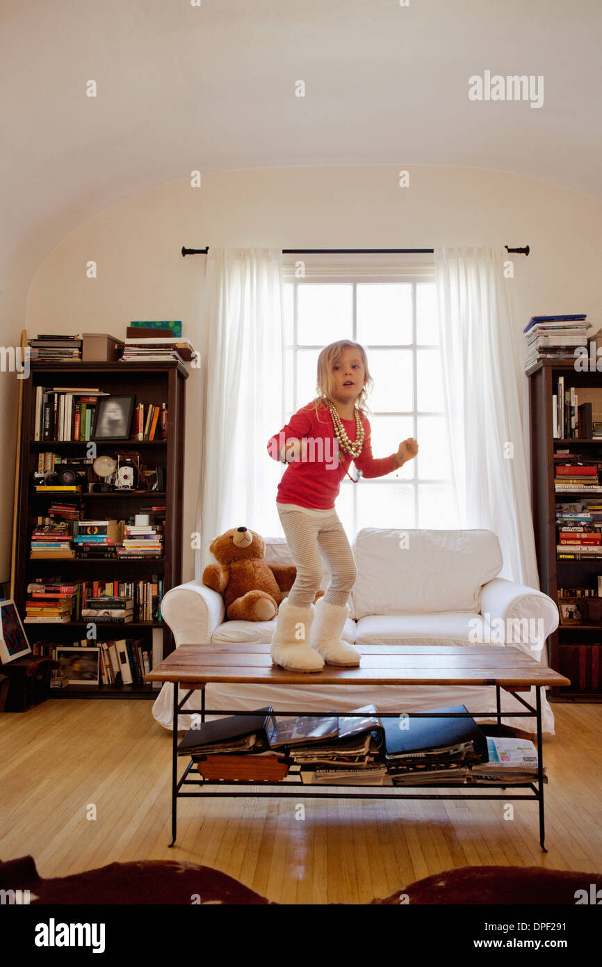 Young girl dancing on top of coffee table - Stock Image