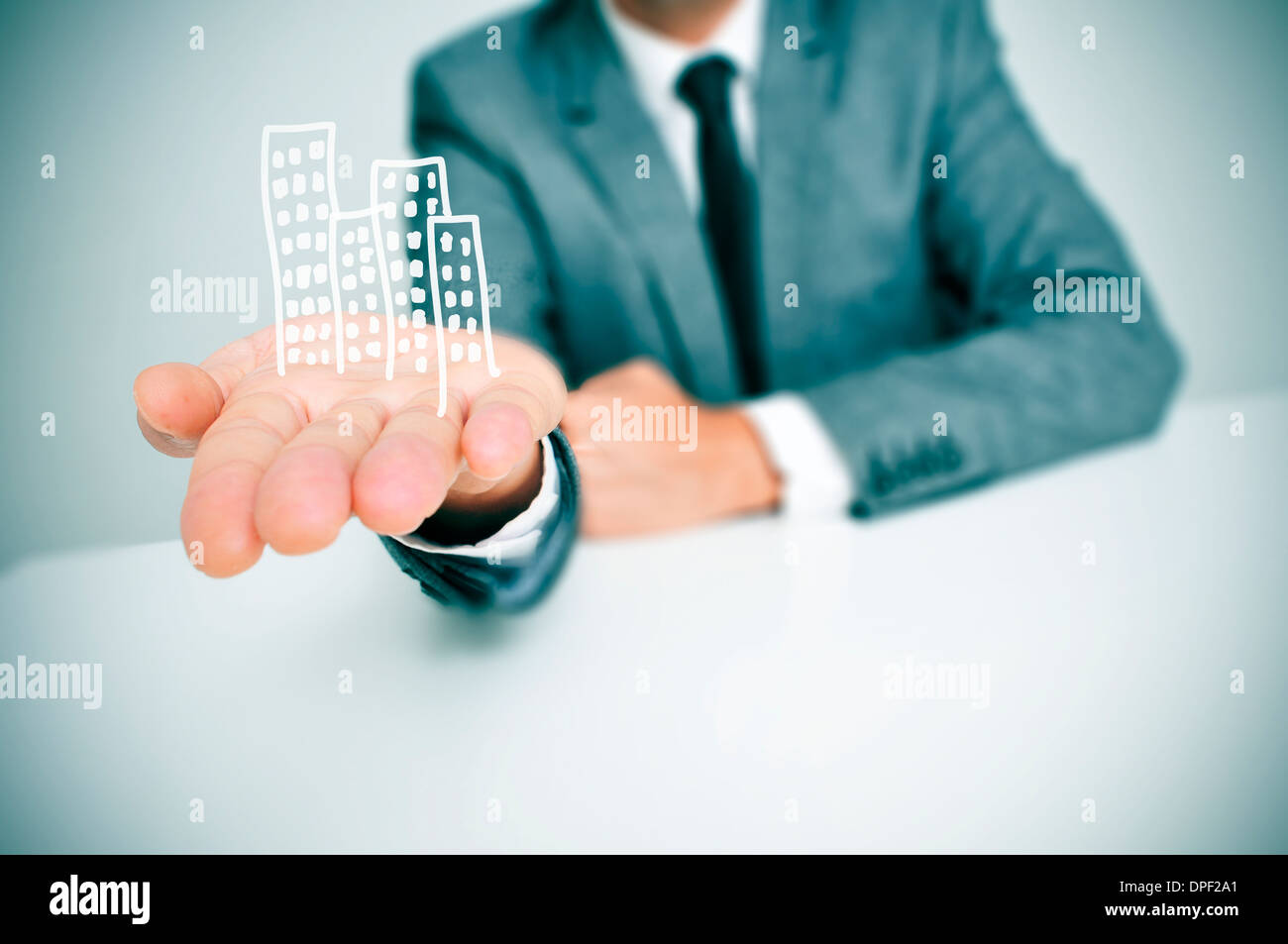 a businessman sitting in a desk showing a pile of drawn buildings in his hand - Stock Image