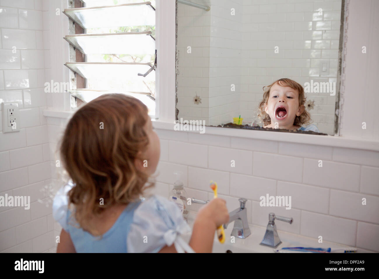 Female toddler looking in mirror cleaning teeth - Stock Image