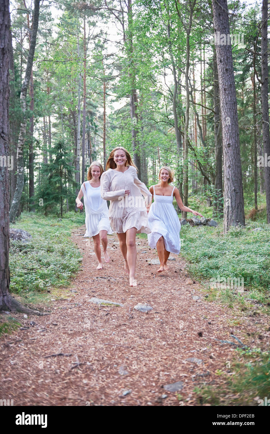 Teenage girls running on forest track - Stock Image