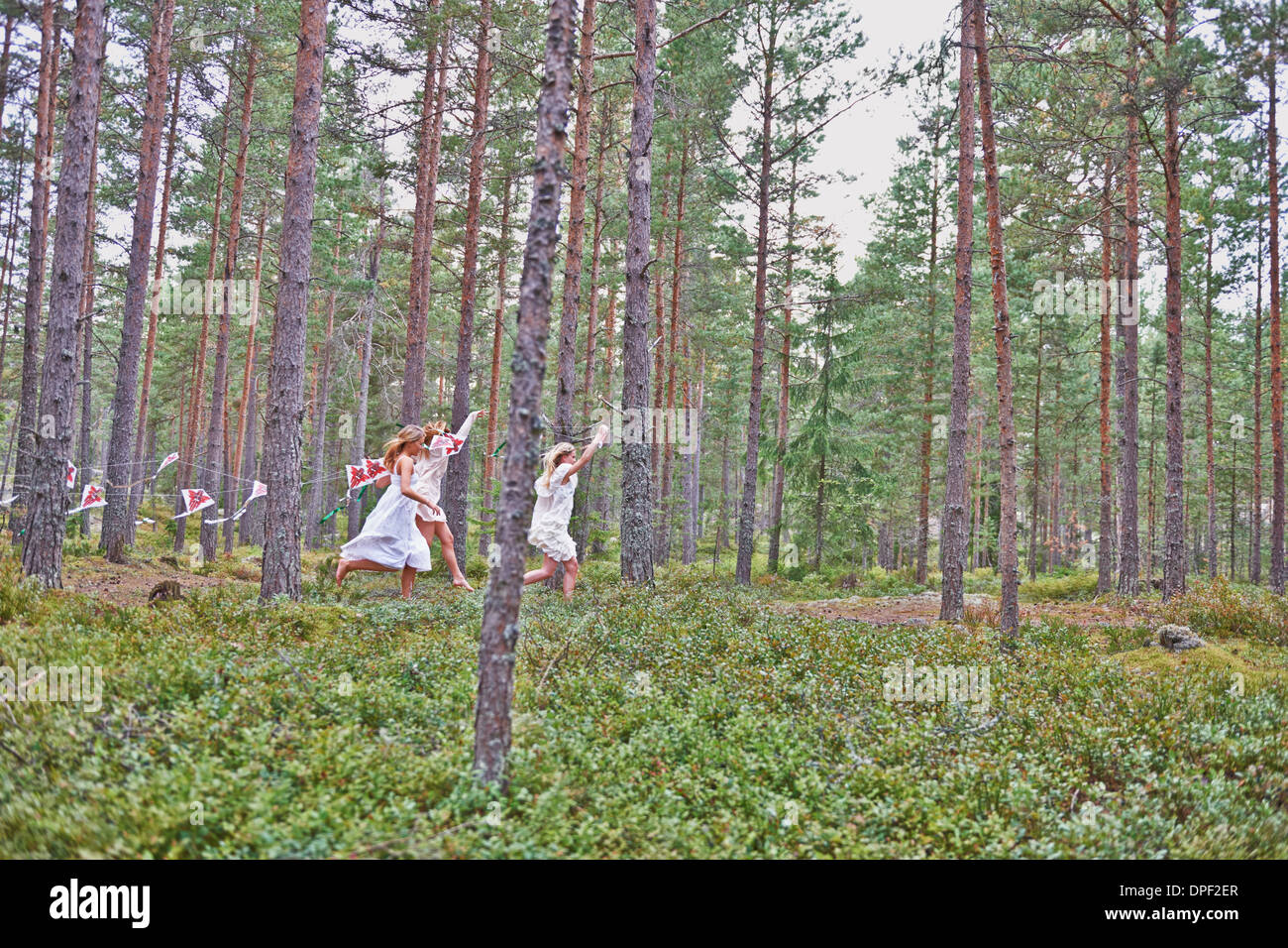 Teenage girls running in forest with kites - Stock Image