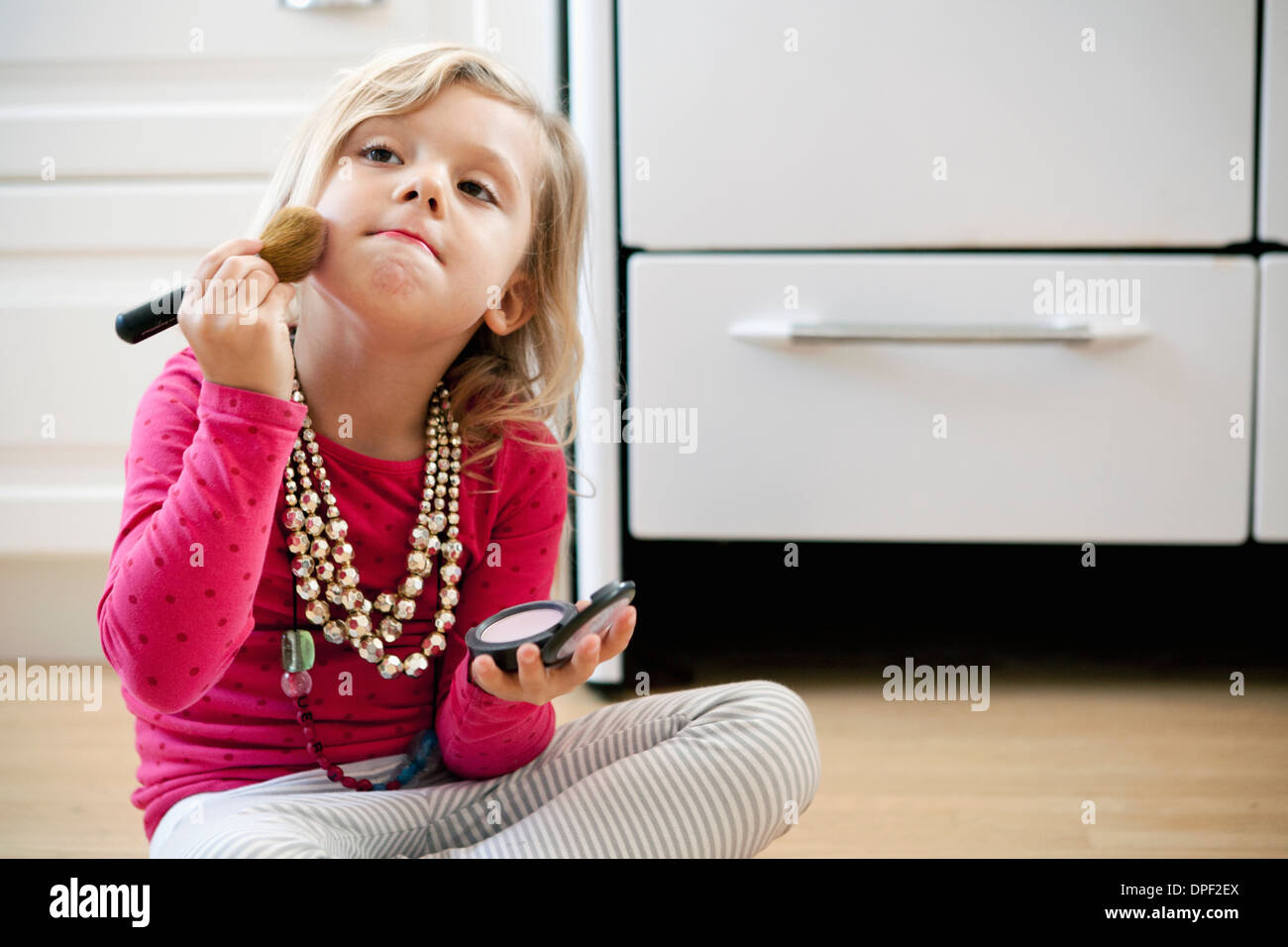 Young girl sitting on kitchen floor with make up - Stock Image