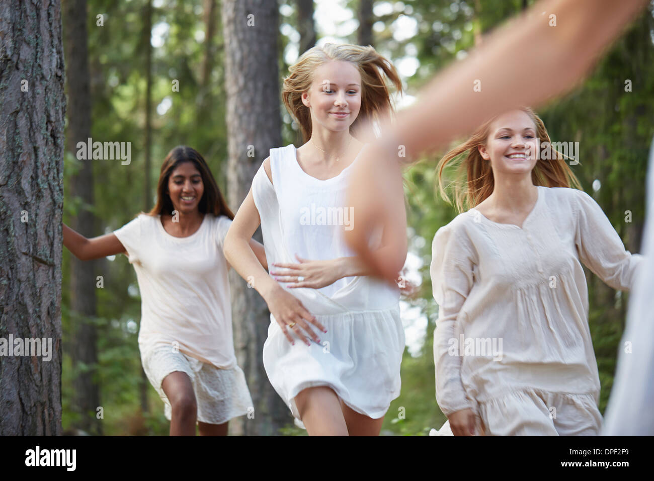 Teenage girls running in forest - Stock Image