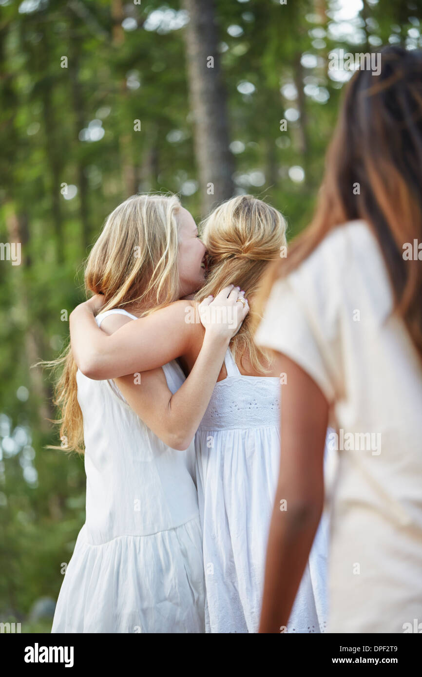 Teenage girls with arm around each other in forest - Stock Image