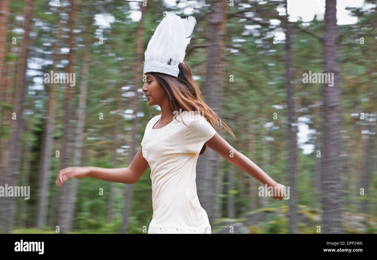 Teenage girl wearing white hat running in forest Stock Photo