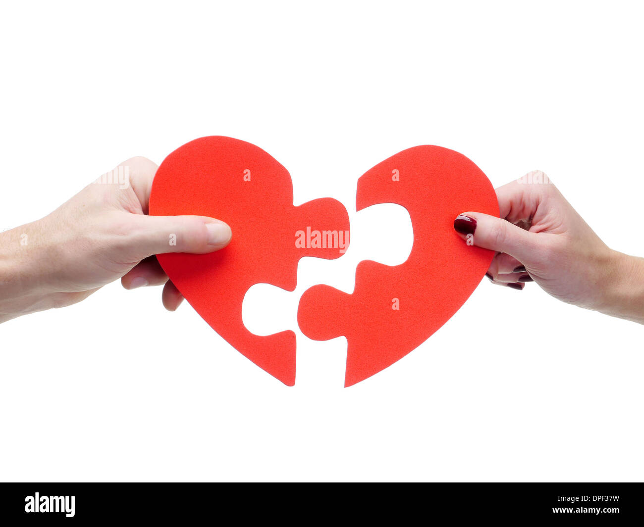 Male and female hand matching red jigsaw heart halves over white background - Stock Image