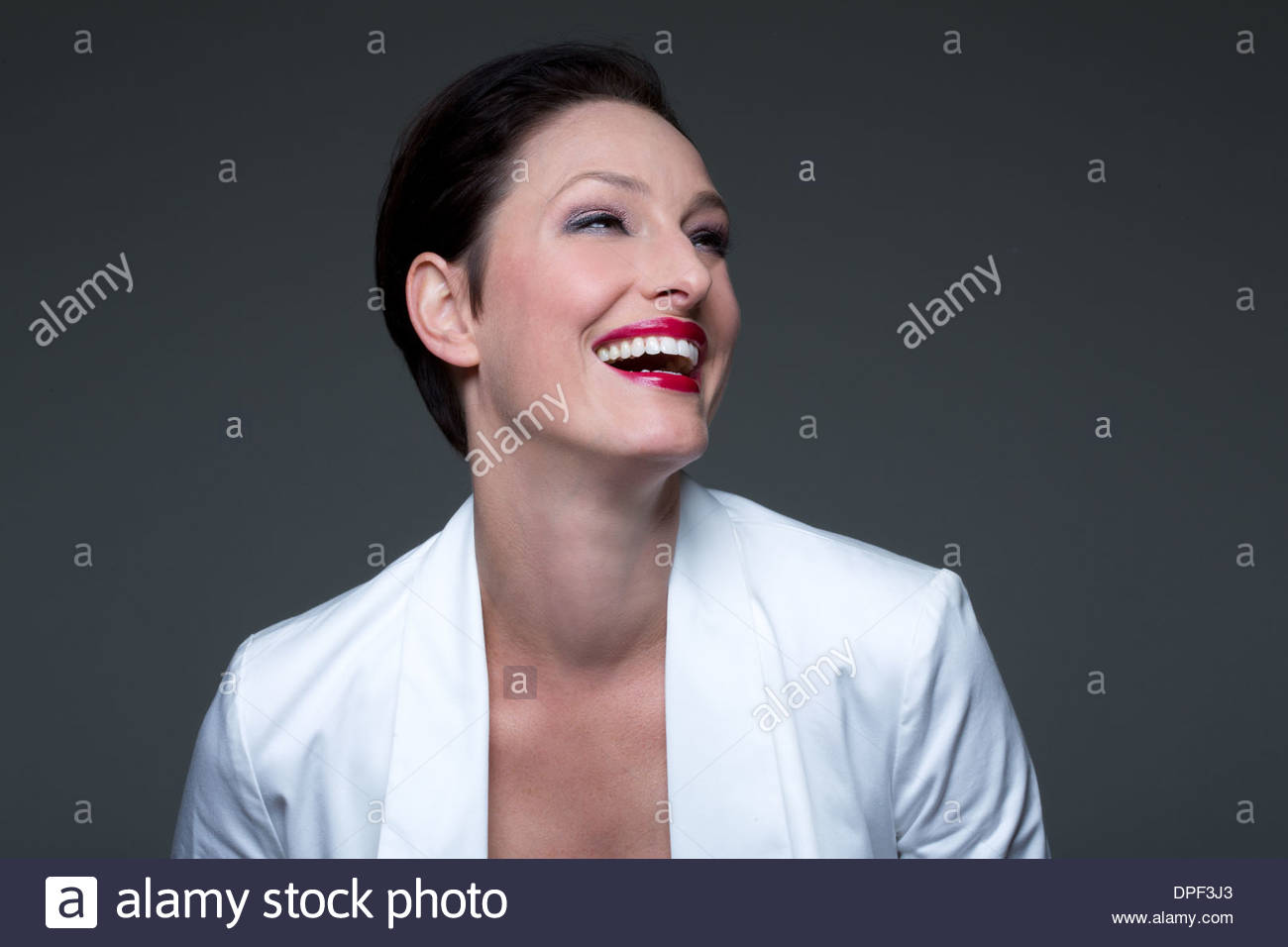 Portrait of mature woman wearing white jacket, laughing - Stock Image