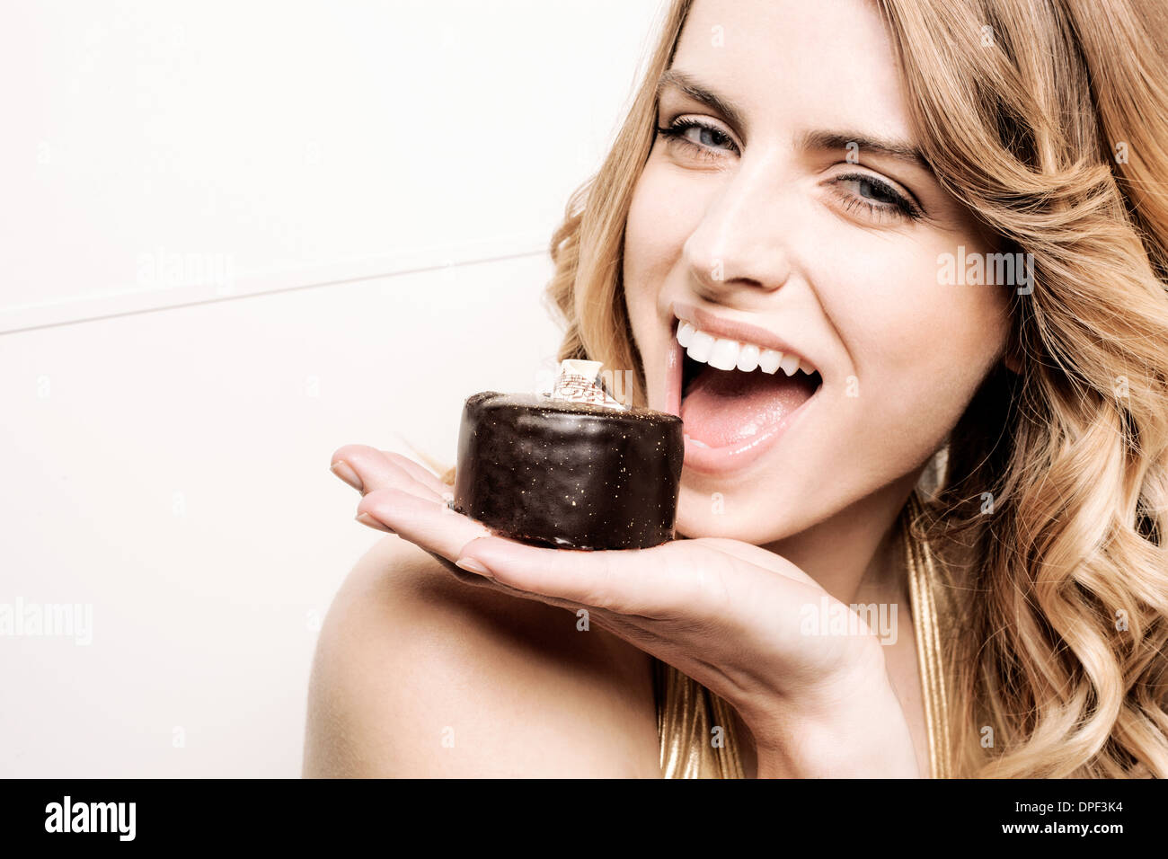 Model holding cake to mouth - Stock Image