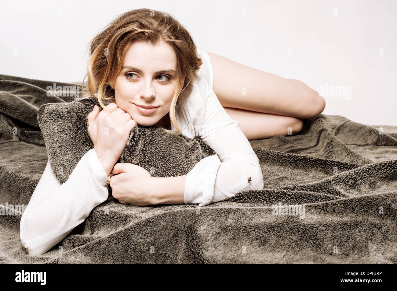 Woman clutching pillow in bed - Stock Image