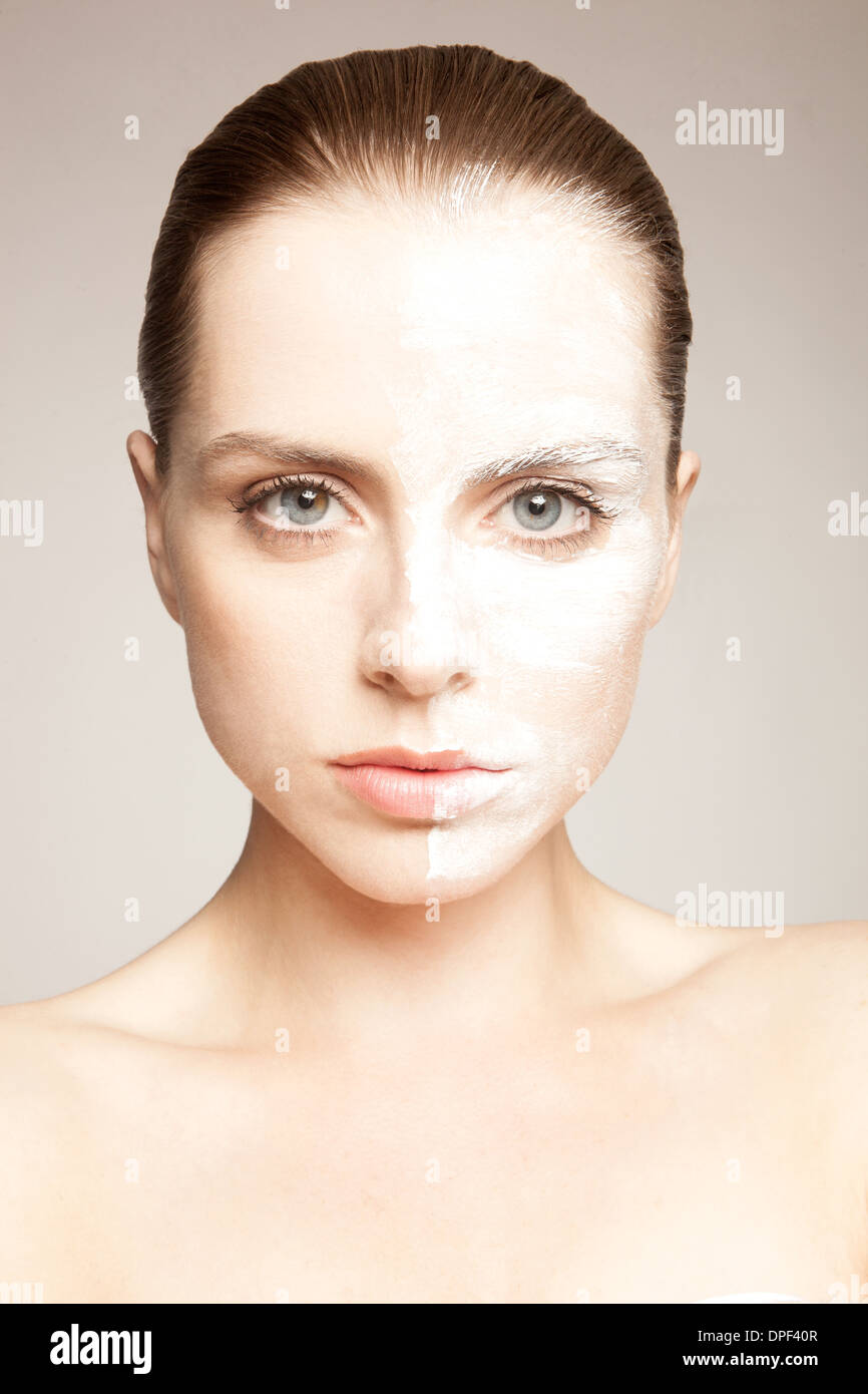 Model with powder on one side of face - Stock Image