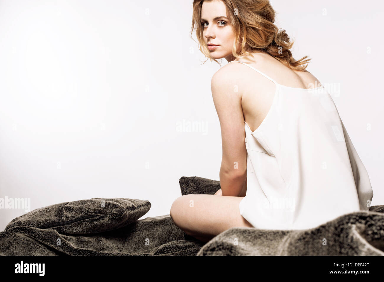 Woman sitting on bed - Stock Image