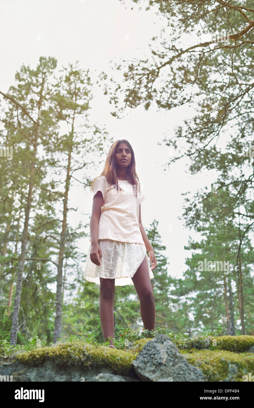Portrait of teenage girl standing in forest - Stock Image
