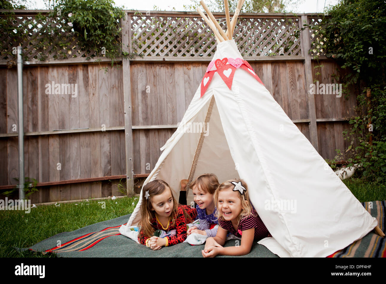 Three young girls lying in teepee in garden - Stock Image