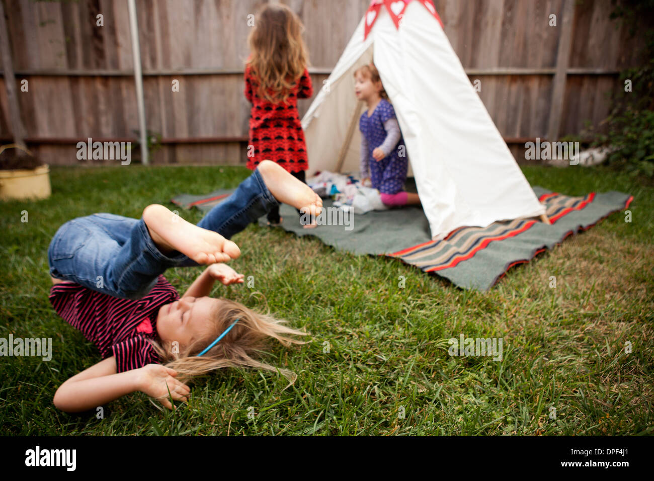 Three young girls playing in garden - Stock Image