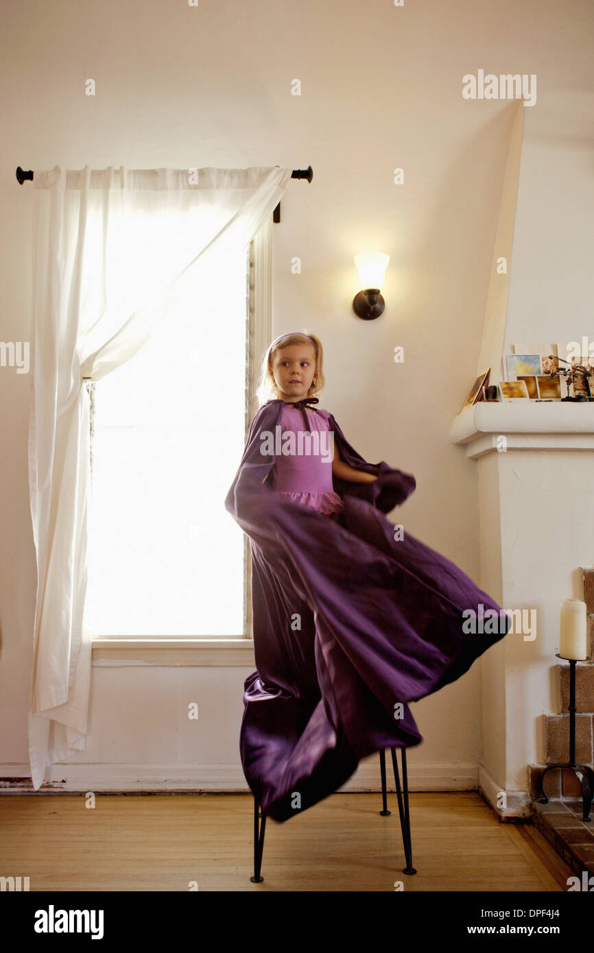 Portrait of young girl standing on chair swinging long cape - Stock Image