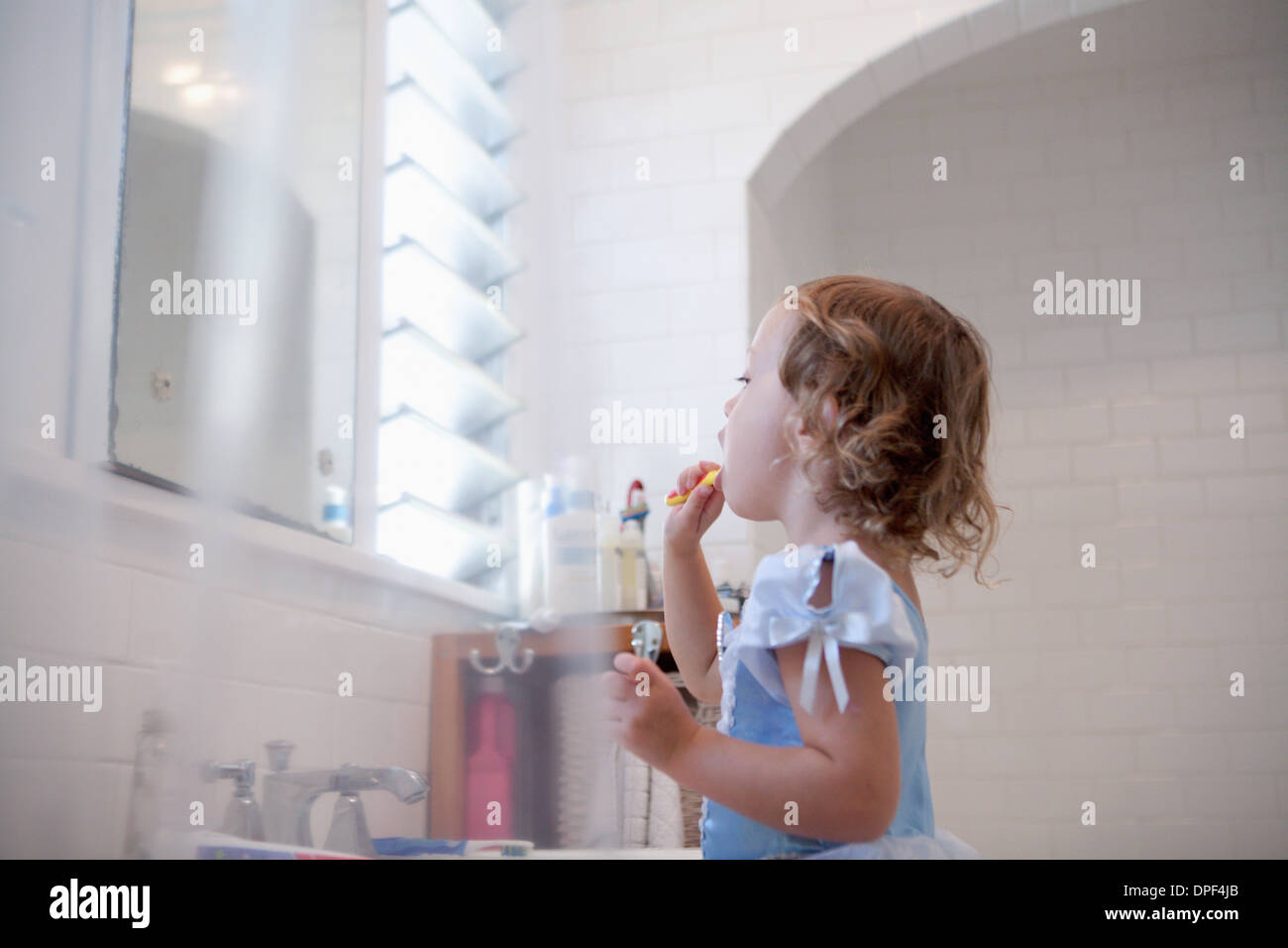 Female toddler cleaning teeth - Stock Image
