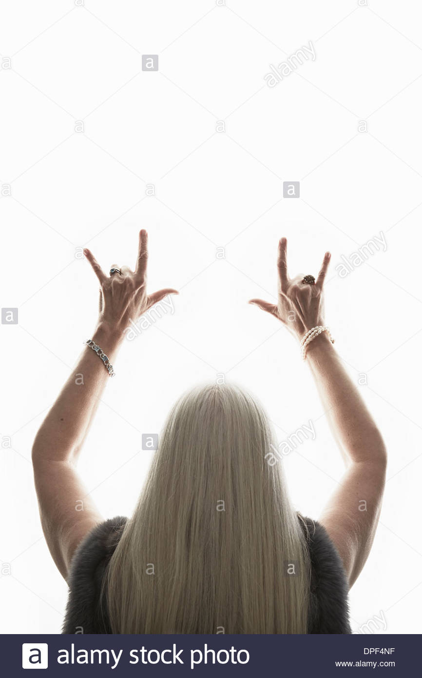 Rear view of senior woman making hand gesture - Stock Image