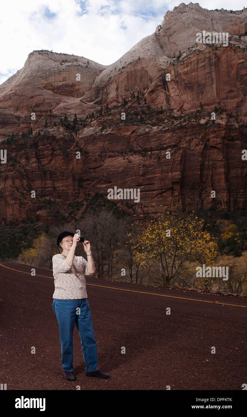 Senior woman taking photograph in Zion National Park, Utah, USA - Stock Image