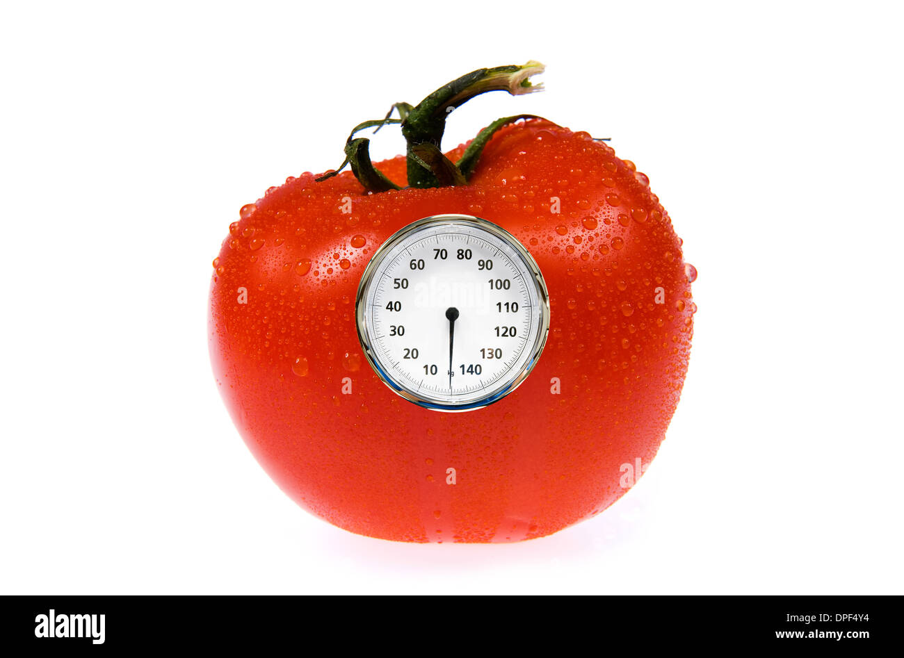 A tomato with a weight scale on it - Stock Image