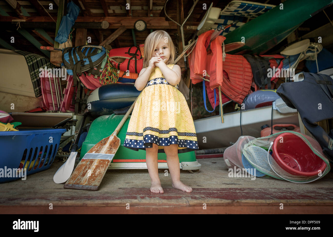 Portrait of female toddler standing at front of storage garage - Stock Image