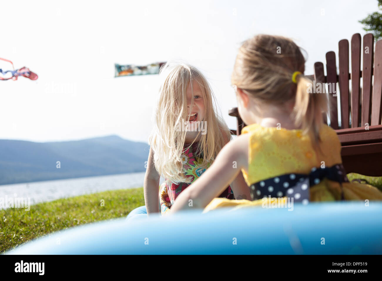 Two female toddlers sitting on air bed, Silver Bay, New York, USA - Stock Image