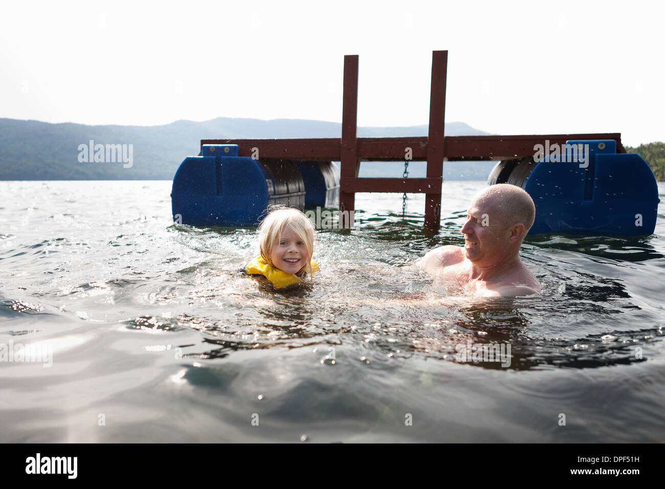 Father and toddler daughter swimming in lake, Silver Bay, New York, USA - Stock Image