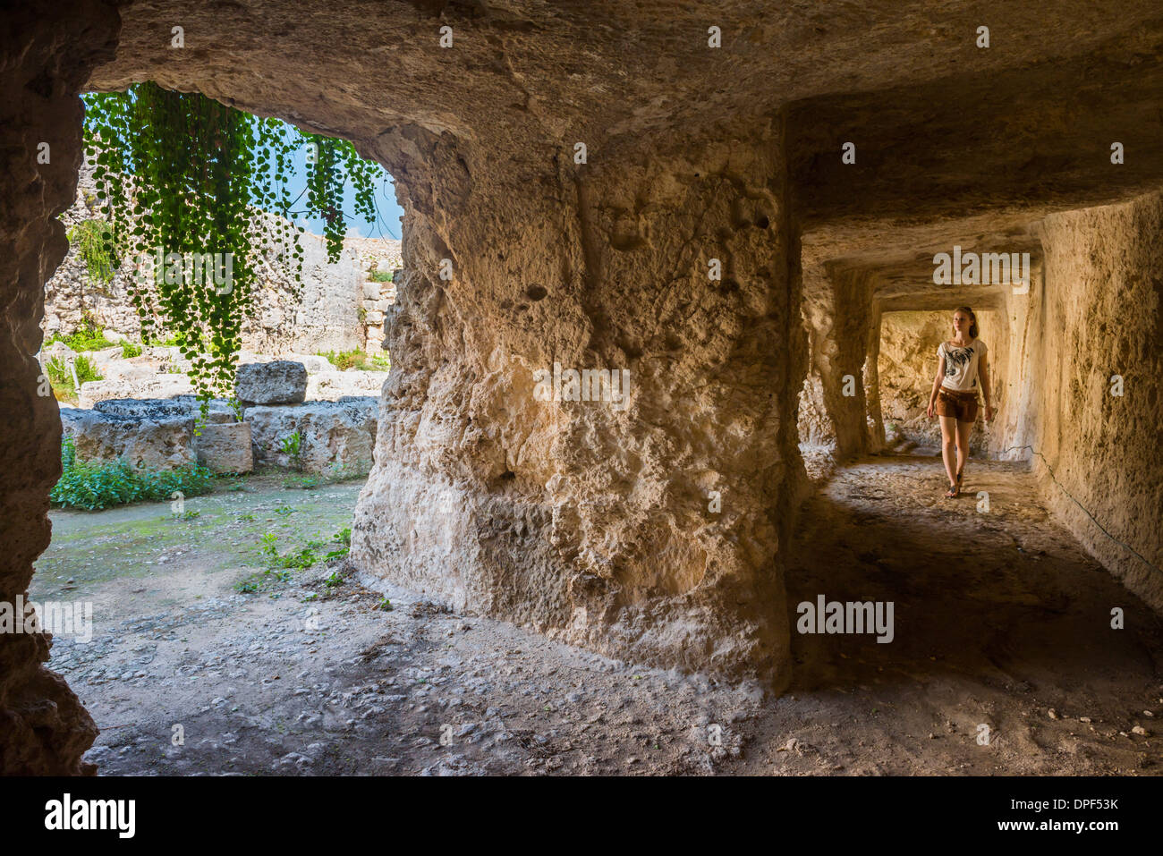 Tourist exploring the tunnels at the Greek ruins, Eurialo Casle (Castello Eurialo), Syracuse (Siracusa), Sicily, Italy, Europe - Stock Image