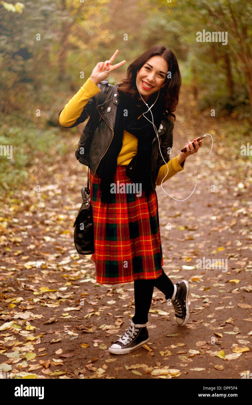 Young woman in park, listening to music using earphones, making peace sign - Stock Image