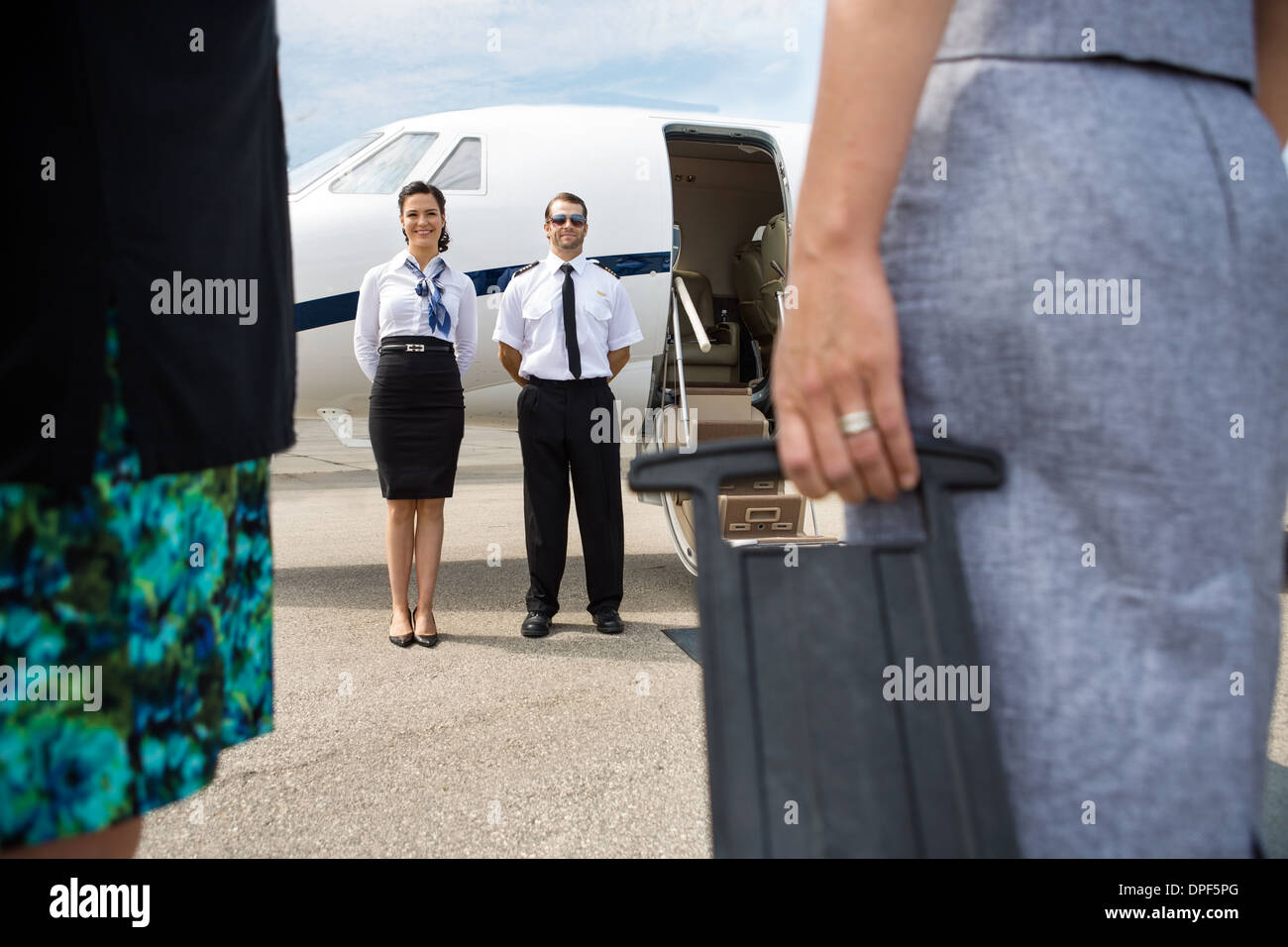 Pilot And Airhostess Standing Near Private Jet - Stock Image