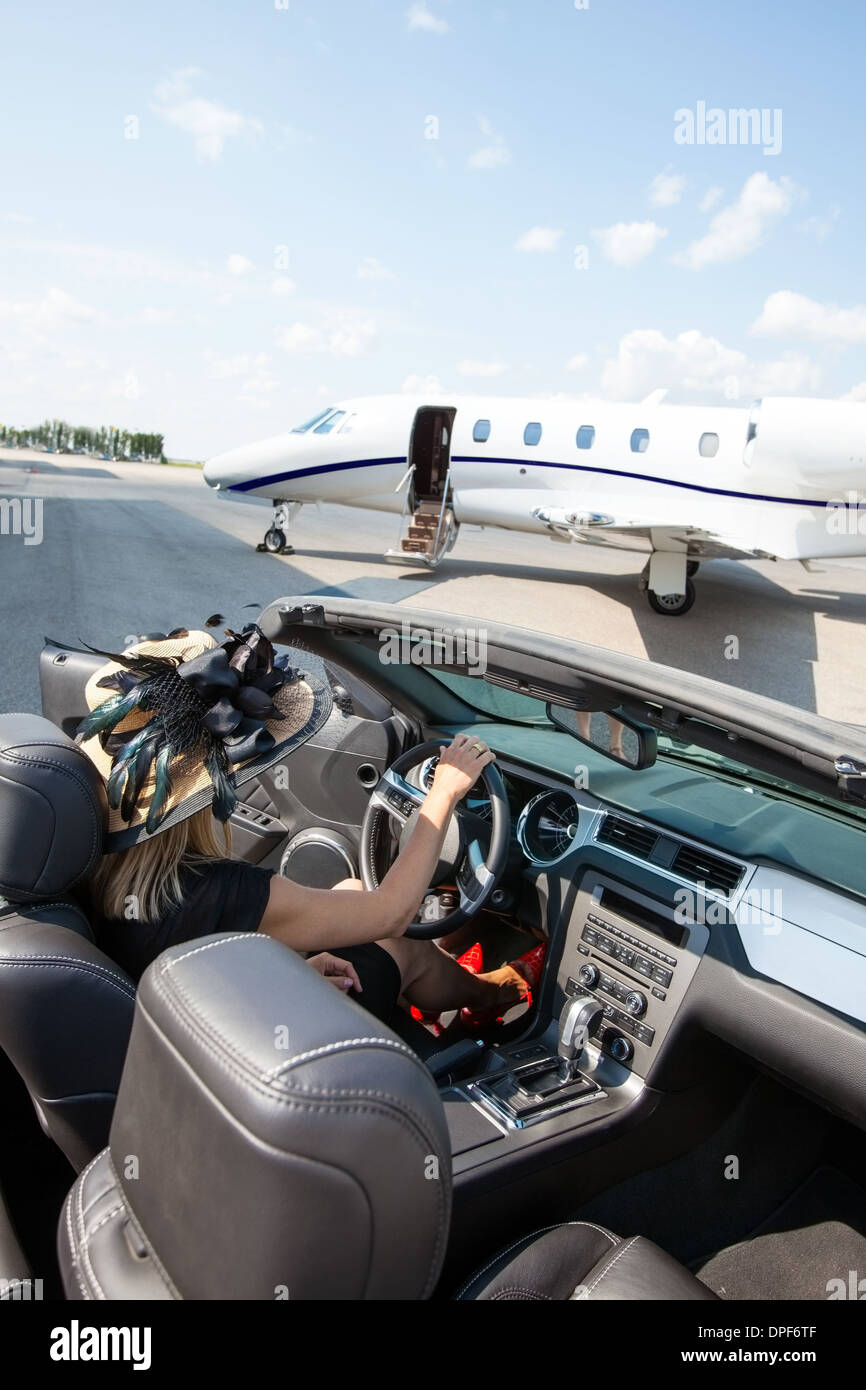 Woman In Convertible With Private Jet At Terminal - Stock Image