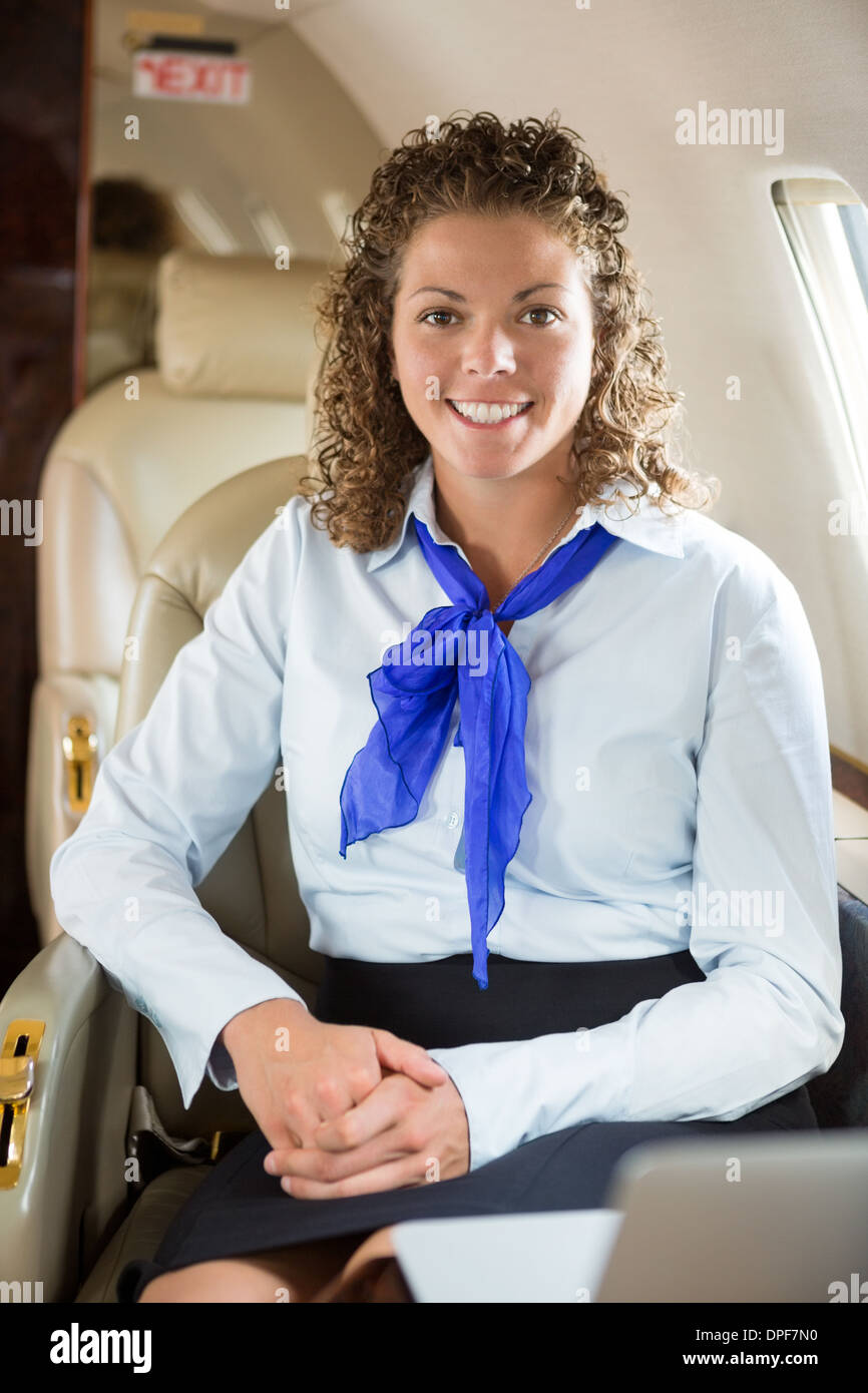 Happy Airhostess Sitting In Private Jet - Stock Image