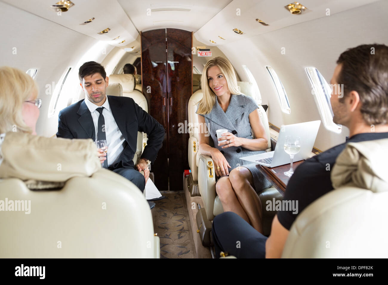 Business People Having Drinks On Private Jet - Stock Image