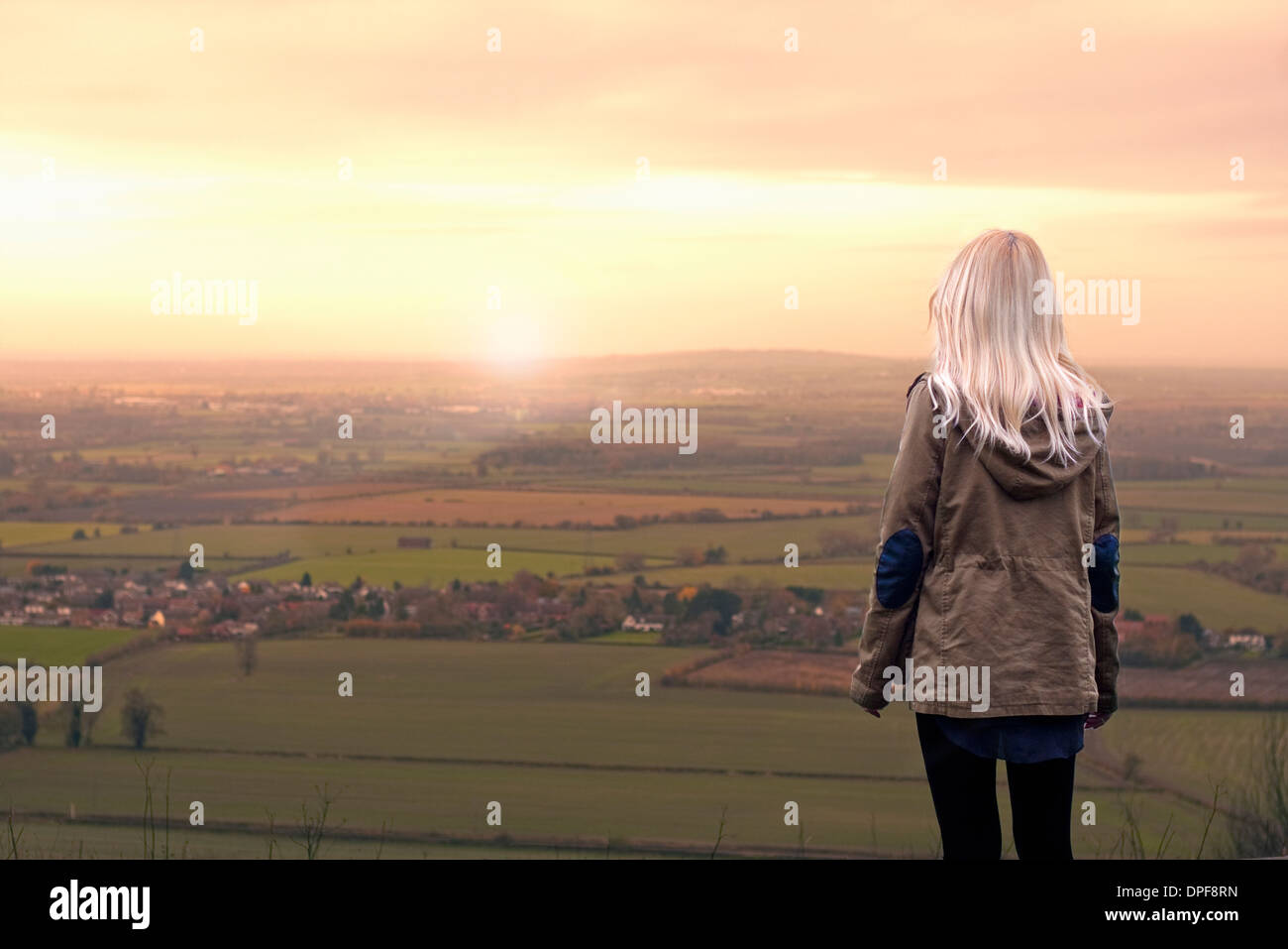 Young woman watching sunrise over rural landscape - Stock Image