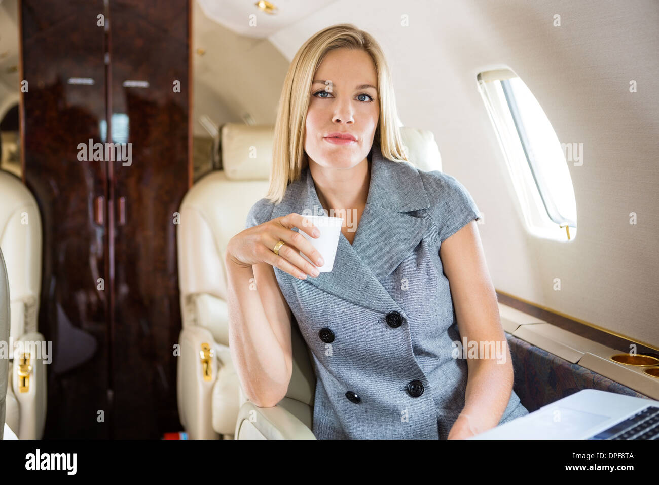 Confident Businesswoman Having Coffee In Private Jet - Stock Image