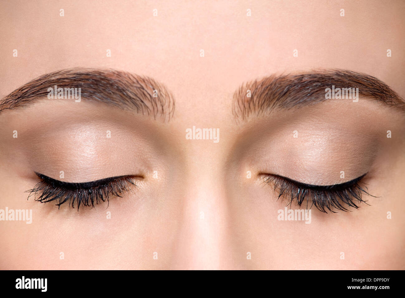 Cropped studio shot of beautiful young woman with eyes closed - Stock Image