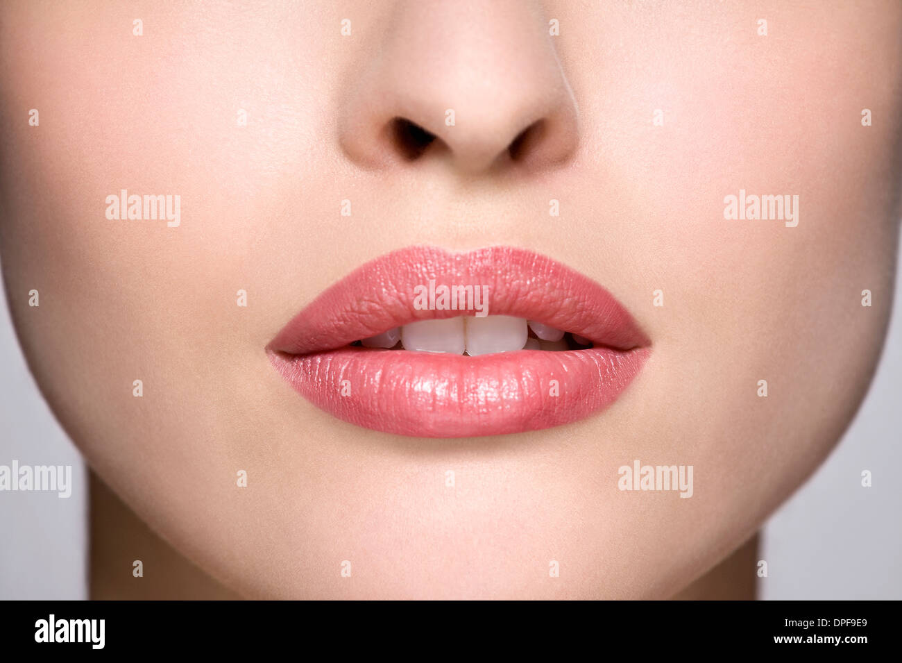 Cropped studio shot of young woman's mouth - Stock Image