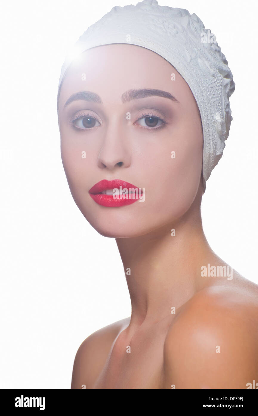 Studio portrait of young woman wearing bathing cap - Stock Image